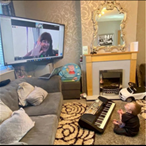 Music therapist who is visible on a TV screen waves at a child sitting in front of a keyboard